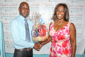 June Isaacs (Gregory Isaacs Foundation) presents David Reid (Eastern Regional Manager JCDC) with a gift basket